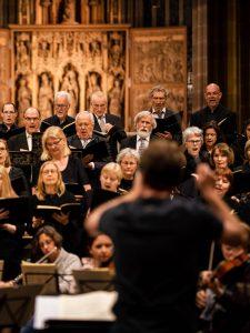 Sängerinnen und Sänger werden vom Dirigenten angeleitet